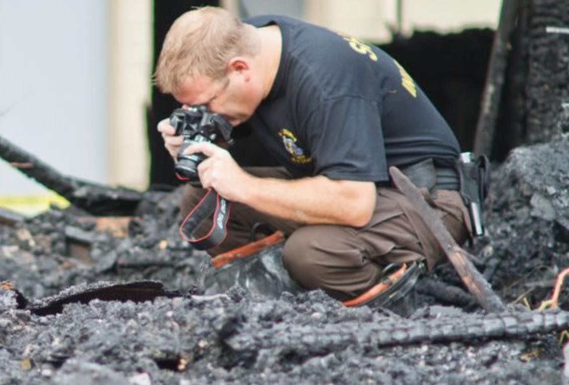 Пожарный дознаватель фотографирует предполагаемое место начала возгорания